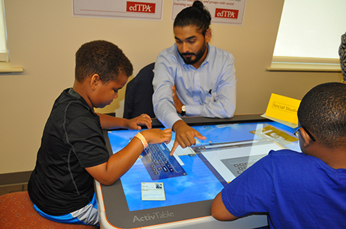 Man helping young boy use Activtable
